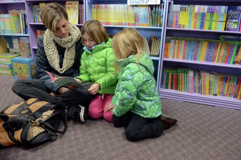 Jill Egan, of Trumbull, sits in the Children's section at Linda's Story Time in Monroe, Conn. and reads with her daughters Maggie, 7, and Tessa, 5, Saturday, Jan. 4, 2013. Photo: Autumn Driscoll / Connecticut Post