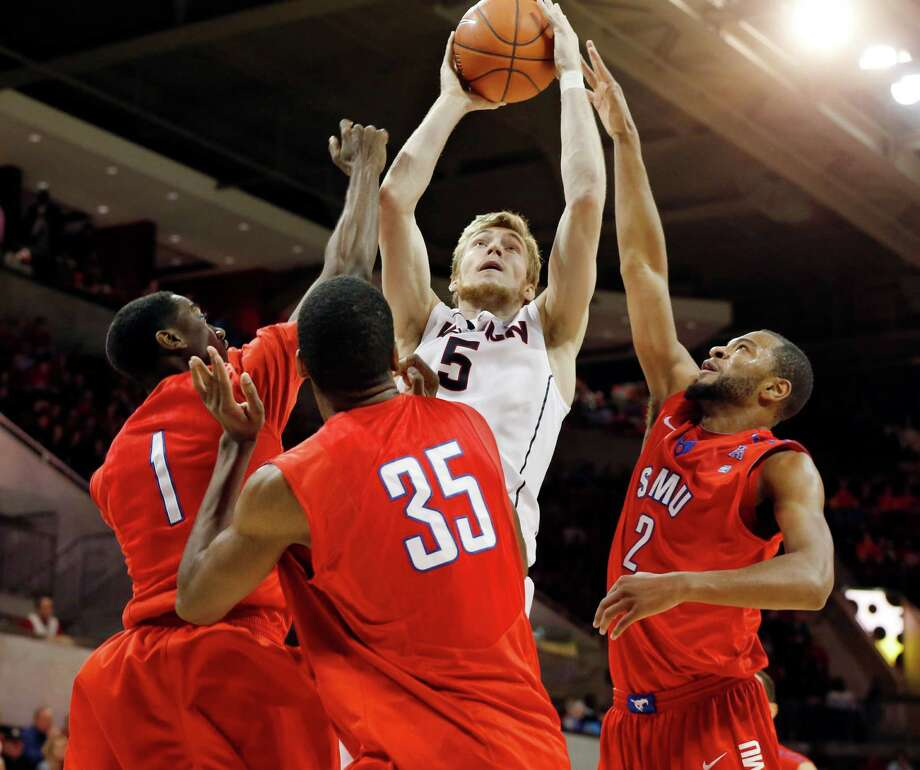 SMU guard Ryan Manuel (1), center Yanick Moreira (35) and forward Shawn Williams (2) gang up to defend a shot by Connecticut guard/forward Niels Giffey (5) during the second half SMU's 74-65 win in an NCAA college basketball game Saturday, Jan. 4, 2014, in Dallas. (AP Photo/John F. Rhodes) Photo: John F. Rhodes, Associated Press / Associated Press