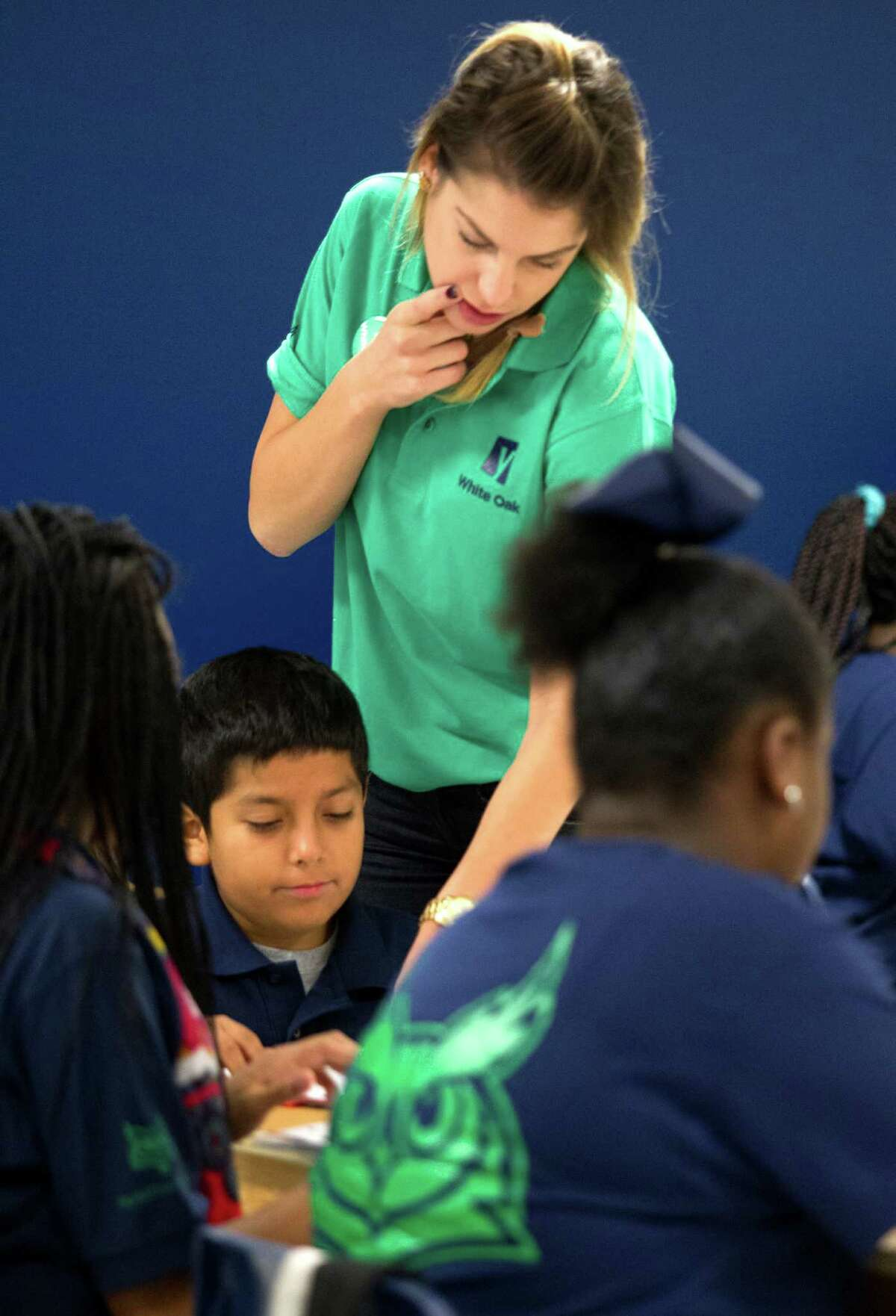 Yes Prep White Oak teacher Colleen Wolanski helps her sixth grade students on a reading problem on Friday, Aug. 30. Two of the largest traditional public school systems in the city �