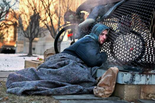 Nick warms himself on a steam grate with three other homeless men by the Federal Trade Commission, just blocks from the Capitol, during frigid temperatures in Washington, Saturday, Jan. 4, 2014. A winter storm that swept across the Midwest this week blew through the Northeast on Friday, leaving bone-chilling cold in its wake.  Photo: Jacquelyn Martin, STF / AP