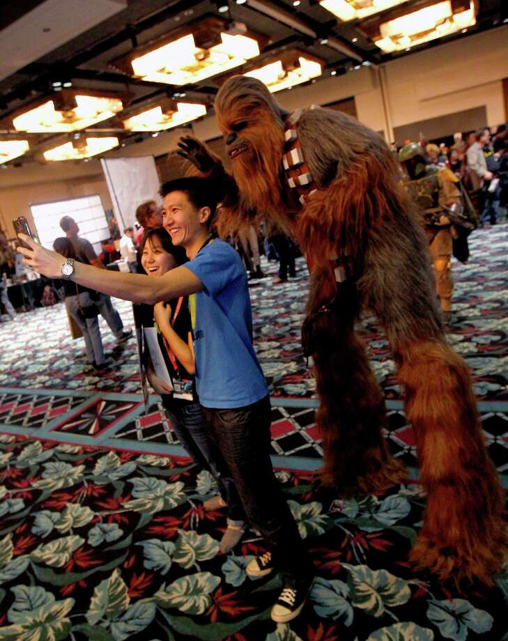 Esther Kim and Oscar Le, from Houston are photo bombed by  Clinton Beasley, Chewbacca at Space City Con held at Moody Gardens Hotel, Spa and Convention Center, in Galveston, Texas. Photo: Thomas B. Shea, The Houston Chronicle / © 2014 Thomas B. Shea