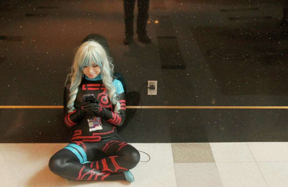 Desiree Allen, of La Porte, dressed as the evil Anti Spiral Nia from the Netflix show Gurren Lagann text on her phone in the hallway at Space City Con held at  Moody Gardens Hotel, Spa and Convention Center, in Galveston, Texas. Photo: Thomas B. Shea, The Houston Chronicle / © 2014 Thomas B. Shea