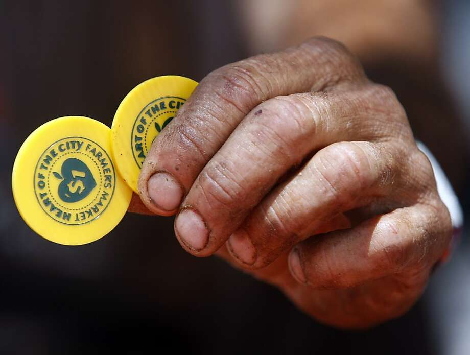 Lack of food aid, like these tokens for a farmer's market, can worsen health at the end of the month. Photo: Paul Chinn, The Chronicle