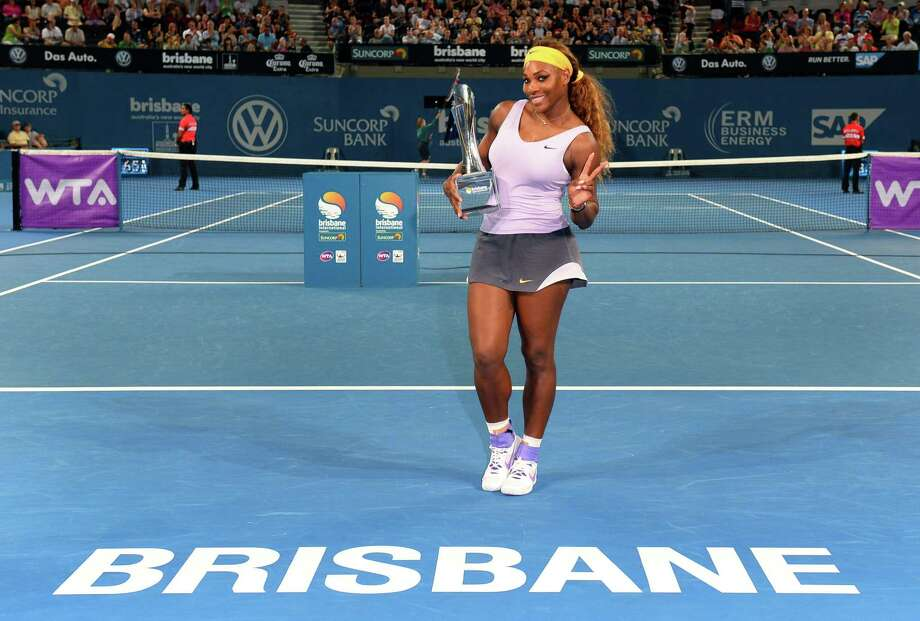 Serena Williams strikes a peaceful pose with her new hardware after claiming the Brisbane International title Saturday. Photo: WILLIAM WEST, Staff / AFP