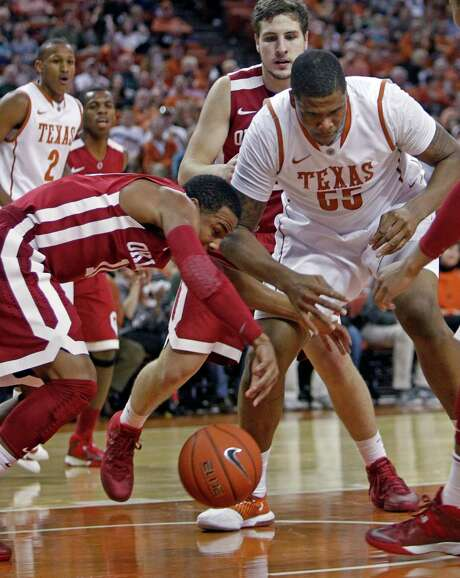 Oklahoma's Isaiah Cousins (11) swipes a loose ball away from Texas' Cameron Ridley in the Sooners' 82-78 win over the Longhorns on Saturday in Austin. Photo: Michael Thomas, FRE / FR65778 AP