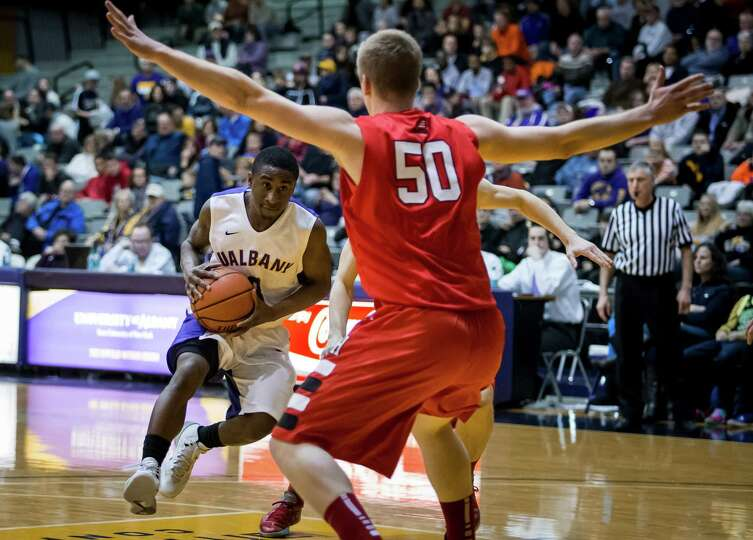 UAlbany's DJ Evans #03 charges past Hartford defenders during UAlbany's America East opening game, S