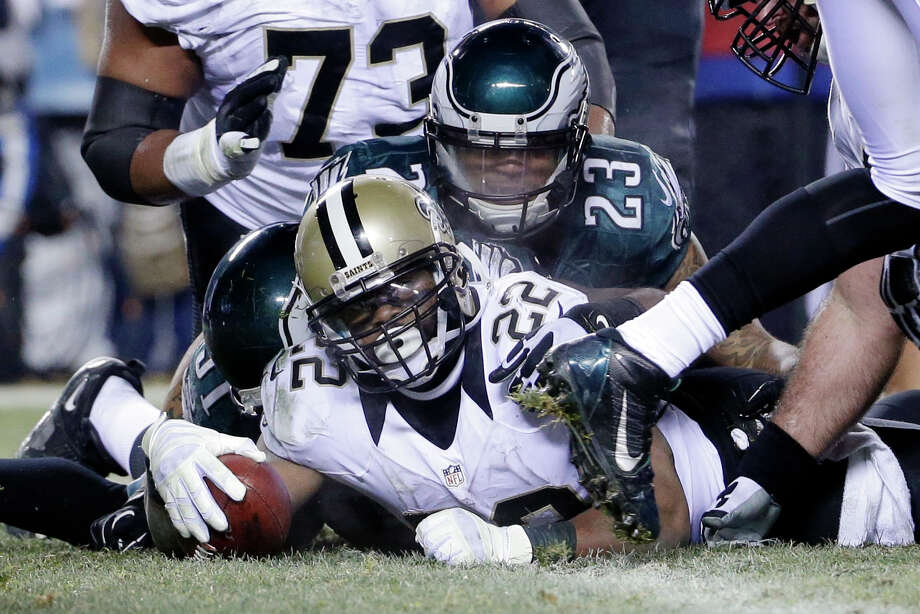New Orleans Saints' Mark Ingram (22) scores a touchdown as Philadelphia Eagles' Patrick Chung (23) defends during the second half of an NFL wild-card playoff football game, Saturday, Jan. 4, 2014, in Philadelphia. (AP Photo/Matt Rourke) ORG XMIT: PXE123 Photo: Matt Rourke / AP