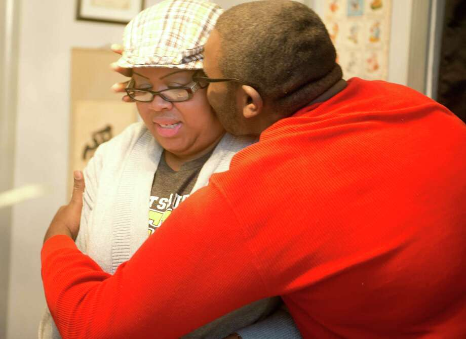 Tommika Police gets a hug from her 16-year-old son Tamir on Tuesday at their home in Bridgeport. Police is unemployed and fears the repercussions of losing unemployment benefits. Photo: Autumn Driscoll / Connecticut Post