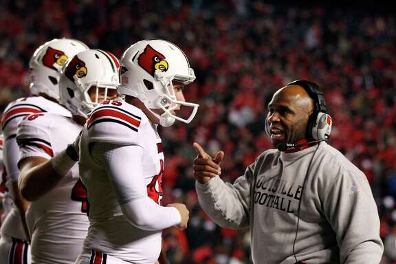 Charlie Strong, right, worked wonders at Louisville, winning 23 games over the past two seasons.