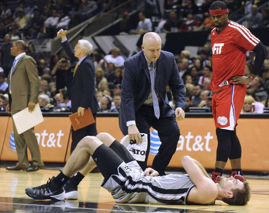 Tiago Splitter of the San Antonio Spurs lies on the ground with a sprained shoulder as head trainer Will Sevening checks on him during second-half NBA action in the AT&T Center on Saturday, Jan. 4, 2014. Stephen Jackson of the Los Angeles Clippers, who used to play for the Spurs, watches. Photo: San Antonio Express-News