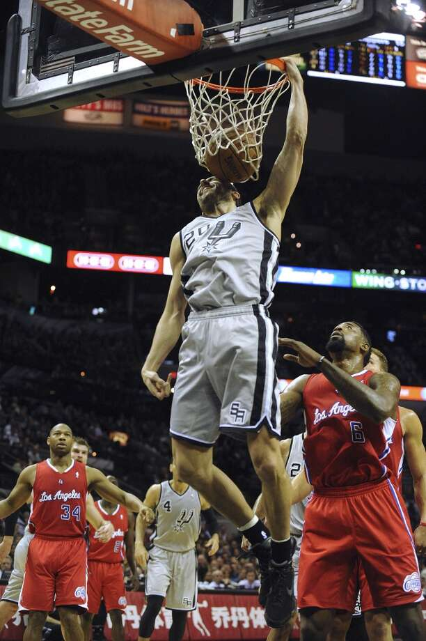 Manu Ginobili of the San Antonio Spurs dunks as Maalik Wayns of the Los Angeles Clippers watches during first-half NBA action in the AT&T Center on Saturday, Jan. 4, 2014. Photo: San Antonio Express-News