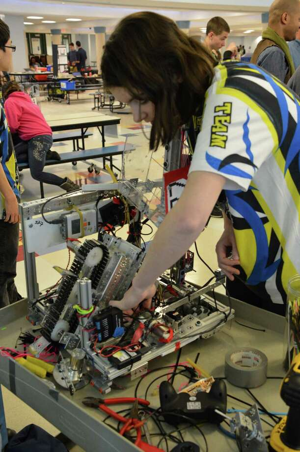 Madeline Schemel, 16, of Westport, makes last-minute adjustments on the Wreckers Robotics robot Saturday. Photo: Jarret Liotta / Westport News contributed