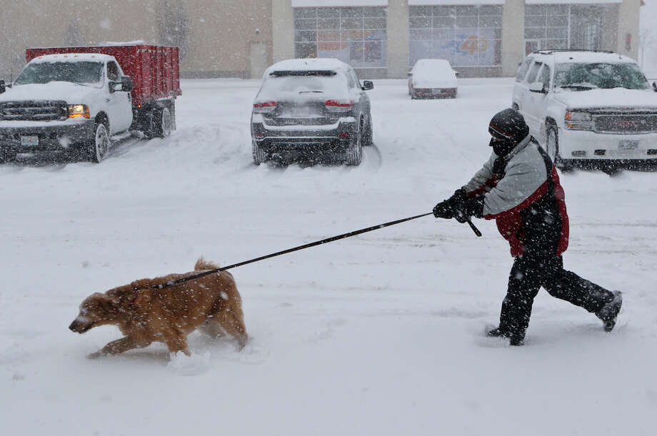 "A ""polar vortex"" is bringing below-zero temperatures to much of the nation this week, likely setting records. Ryan Metcalf tries to hang on to his golden retriever, Daisy, on Sunday, Jan. 5, 2014, in Brentwood, Mo. Photo: J.B. Forbes, AP / St. Louis Post-Dispatch"