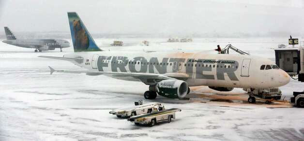 A crew works to de-ice planes at O'Hare International Airport in Chicago on Sunday, Jan. 5, 2014. In Chicago, temperatures were expected to fall throughout Sunday to about 11 degrees by 5 p.m. About 1,200 flights had been cancelled Sunday morning at O'Hare and Midway international airports in Chicago, aviation officials said. Photo: Nam Y. Huh, AP  / AP2014