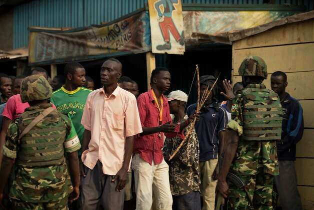 A Burundian peacekeeper gestures to a man carrying a homemade bow and arrow to stay back, as groups of armed Christians and Muslims faced off across a traffic circle in the 5th Arron