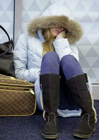 Anna Maksimkina of Yekaterinburg, Russia, sleeps on the floor at Kennedy International Airport after a Delta flight from Toronto to New York skidded off the runway into a snow bank, temporarily halting all flights, Sunday, Jan. 5, 2014, in New York. Authorities have said to to expect delays and flight cancellations because of the cold temperatures. Photo: Kathy Willens, AP  / AP