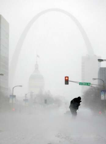 A person struggles to cross a street in blowing and falling snow as the Gateway Arch appears in the distance Sunday, Jan. 5, 2014, in St. Louis. Snow that began in parts of Missouri Saturday night picked up intensity after dawn Sunday with several inches of snow on the ground by midmorning and more on the way. Photo: Jeff Roberson, AP  / AP2014