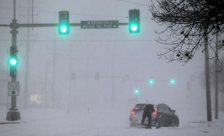 A driver tries to get his car moving in St. Louis, which had about a foot of snow by Sunday afternoon. Windchill warnings stretch from Montana to Alabama. Photo: Robert Cohen, Associated Press