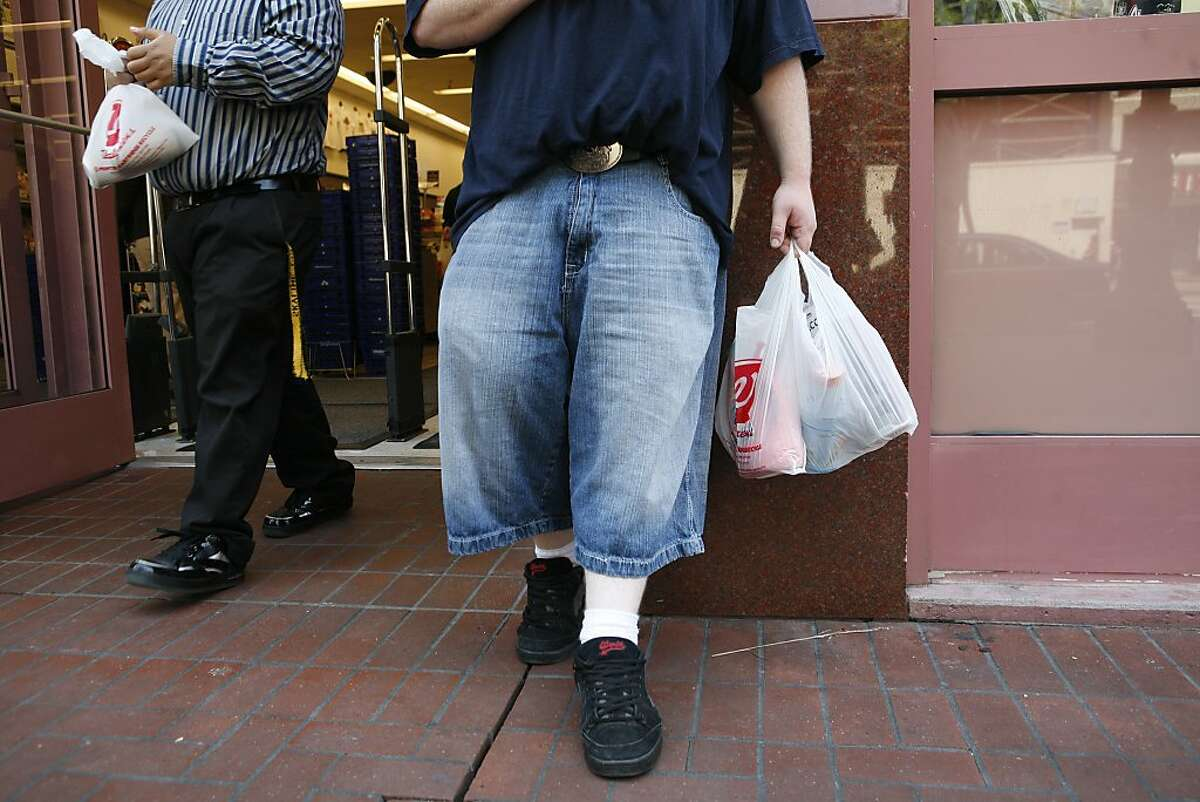 Luther Carr, (right) of San Francisco, holds newly purchased goods in a non-biodegradable plastic Walgreens bag front of the 850 Market Street store on Monday May 19, 2008 in San Francisco, Calif. On Monday some of the bags being used where non-recyclable while others were. The store is in the process of phasing out non-degradable plastic bags in preparation for the city-wide ban on them starting May 20, 2008. Photo by Mike Kepka / San Francisco Chronicle