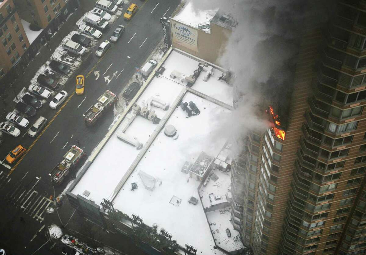 Flames and smoke emerge from the 20th floor of the Strand apartment building near Times Square, Sunday, Jan. 5, 2014 in New York. Authorities say two people have been critically injured in the three-alarm high-rise fire.