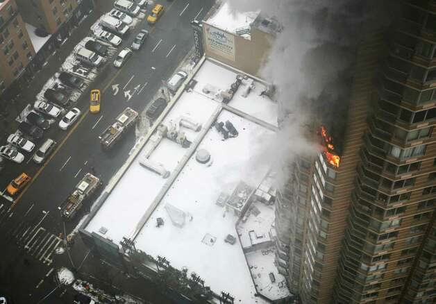 Flames and smoke emerge from the 20th floor of the Strand apartment building near Times Square, Sunday, Jan. 5, 2014 in New York. Authorities say two people have been critically injured in the three-alarm high-rise fire. Photo: Katherine Bourbeau, AP  / AP