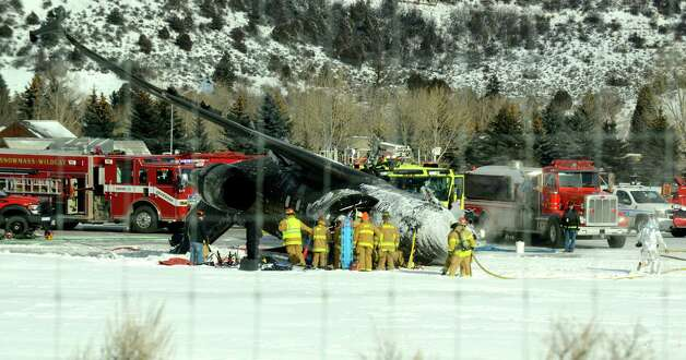 Emergency crews work near a passenger plane that crashed upon landing at the Aspen-Pitkin County Airport in Aspen, Colo., Sunday, Jan. 5, 2014. Photo: Leigh Vogel, AP  / The Aspen Times