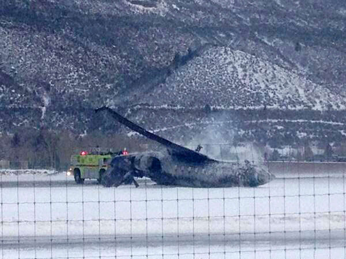 Emergency crews respond as a small plane lies on a runway at Aspen Airport in western Colorado after it crashed upon landing Sunday, Jan. 5, 2014. Emergency crews are responding to a fiery plane crash at Aspen Airport in western Colorado.