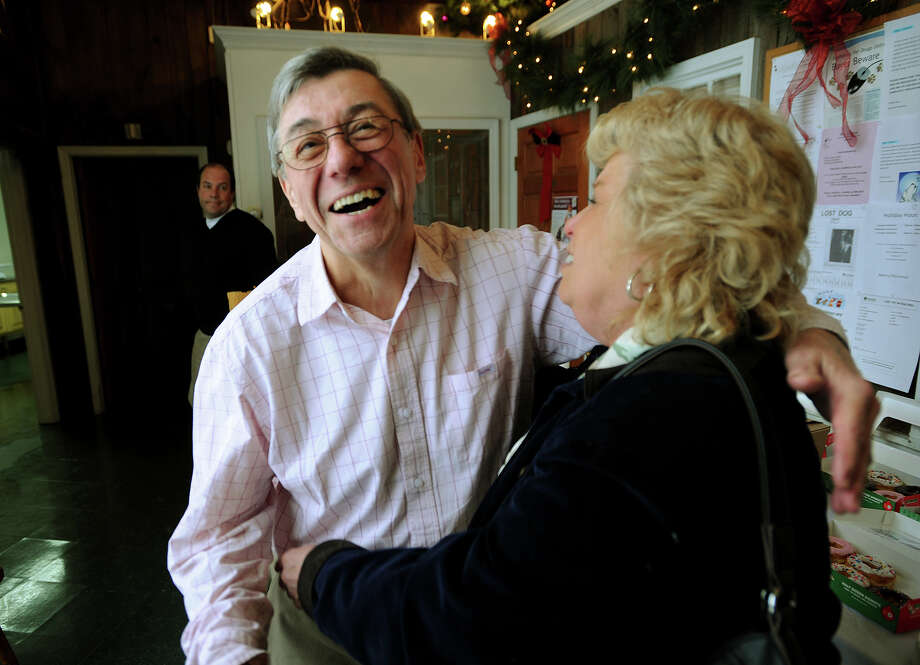 Dr. Alan Busek, left, receives a hug from thirty year customer Maxine Baena, of Shelton, on his final day before retirement at the Pet Hospital of Stratford on Sunday, January 5, 2014. Photo: Brian A. Pounds / Connecticut Post