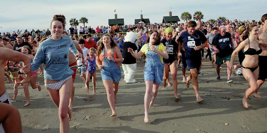 People run to the ocean during the Ocean Lakes 13th annual Polar Bear Plunge at Ocean Lakes Family Campground, in Myrtle Beach, S.C., on Tuesday, Dec. 31, 2013. Each person donated a nonperishable food item that will go to local food banks. Photo: Charles Slate, AP  / The Sun News