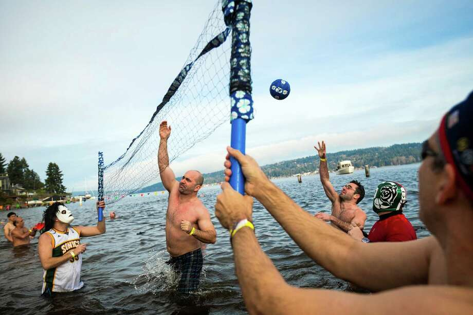 After charging into the frigid waters of Pontiac Bay, a team of attendees began a quick game of pickup volleyball during the 12th Annual Polar Bear Plunge Wednesday, Jan. 1, 2014, at Matthews Beach Park in Seattle, Wash. About 300 people participated in the first Polar Bear Plunge in 2003; since then, attendance has nearly reached 1,000 attendees. Photo: Jordan Stead, AP  / seattlepi.com