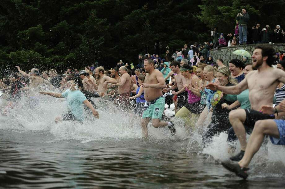Overcast skies, spitting rain and a posted water temperature of 37 degrees could not keep a crowd from turning out to participate in the Polar Plunge, a local New Year's Day tradition, on Wednesday, Jan. 1, 2014, at Auke Bay, Alaska. Photo: Becky Bohrer, AP  / AP