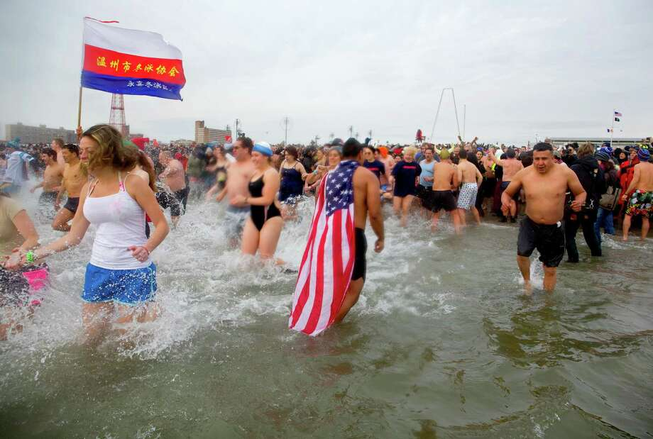 Swimmers enter and exit the frigid waters at Coney Island beach in New York Wednesday, Jan. 1 2014, as they take part in the 111th Annual New Year's Day Polar Bear Plunge. Photo: Craig Ruttle, AP  / FR61802 AP