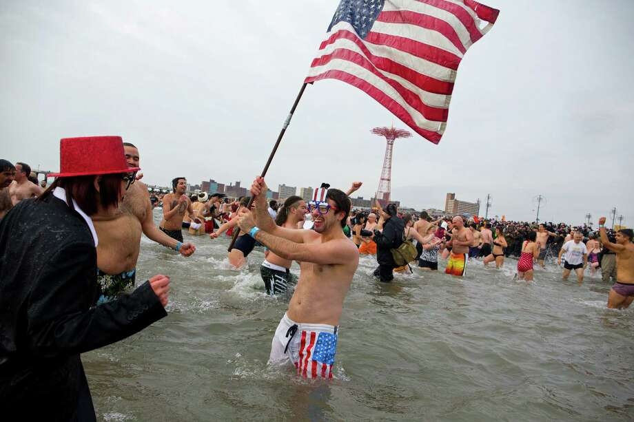 A swimmer waves the American flag after jumping into frigid waters at Coney Island beach in New York Wednesday, Jan. 1 2014, as they take part in the 111th Annual New Year's Day Polar Bear Plunge. Photo: Craig Ruttle, AP  / FR61802 AP