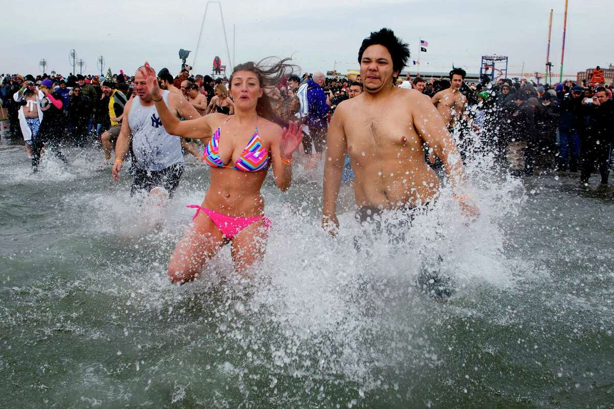 Swimmers jump into frigid waters at Coney Island beach in New York Wednesday, Jan. 1 2014, as they take part in the 111th Annual New Year's Day Polar Bear Plunge.