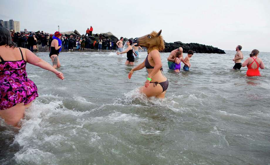 Swimmers, some in unusual costumes, enter and exit the frigid waters at Coney Island beach in New York Wednesday, Jan. 1 2014, as they take part in the 111th Annual New Year's Day Polar Bear Plunge. Photo: Craig Ruttle, AP  / FR61802 AP
