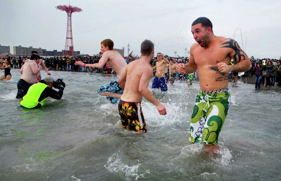 A Swimmers emerges after jumping into the frigid waters at Coney Island beach in New York Wednesday, Jan. 1 2014, as they take part in the 111th Annual New Year's Day Polar Bear Plunge. Photo: Craig Ruttle, AP  / FR61802 AP