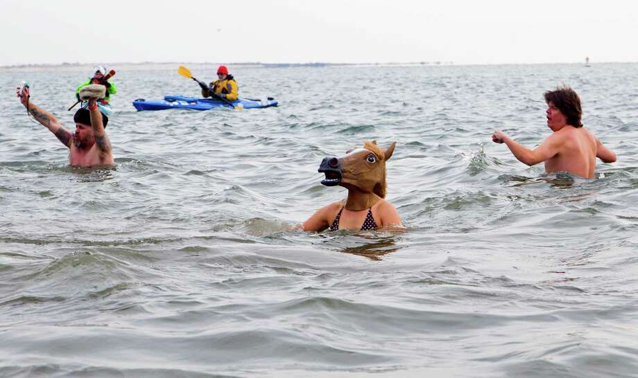Swimmers, some in unusual costume, swim in the frigid waters at Coney Island beach in New York Wednesday, Jan. 1 2014, as they take part in the 111th Annual New Year's Day Polar Bear Plunge. Photo: Craig Ruttle, AP  / FR61802 AP