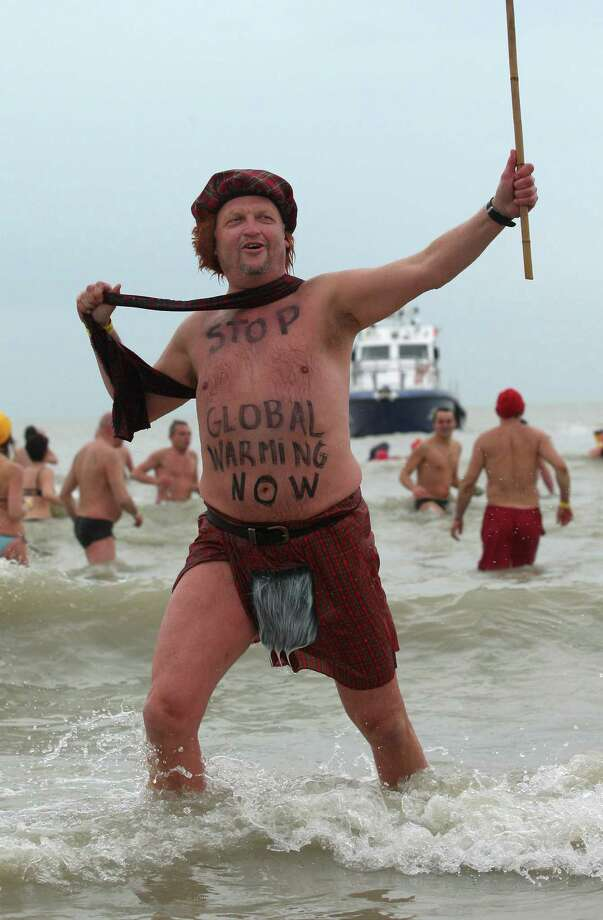A man poses for photographers in the water, at the Belgian North Sea town  of Ostend, Belgium, Saturday, Jan. 4, 2014. Thousands of swimmers jumped and dived into frigid waters as they took part in the annual New Year's plunge into the North Sea. Photo: Yves Logghe, AP  / AP