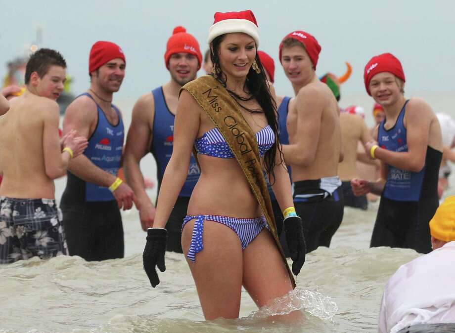 Men stare at a woman, at the Belgian North Sea town of Ostend, Belgium, Saturday, Jan. 4, 2014. Thousands of swimmers jumped and dived into frigid waters as they took part in the annual New Year's plunge into the North Sea. Photo: Yves Logghe, AP / AP2014