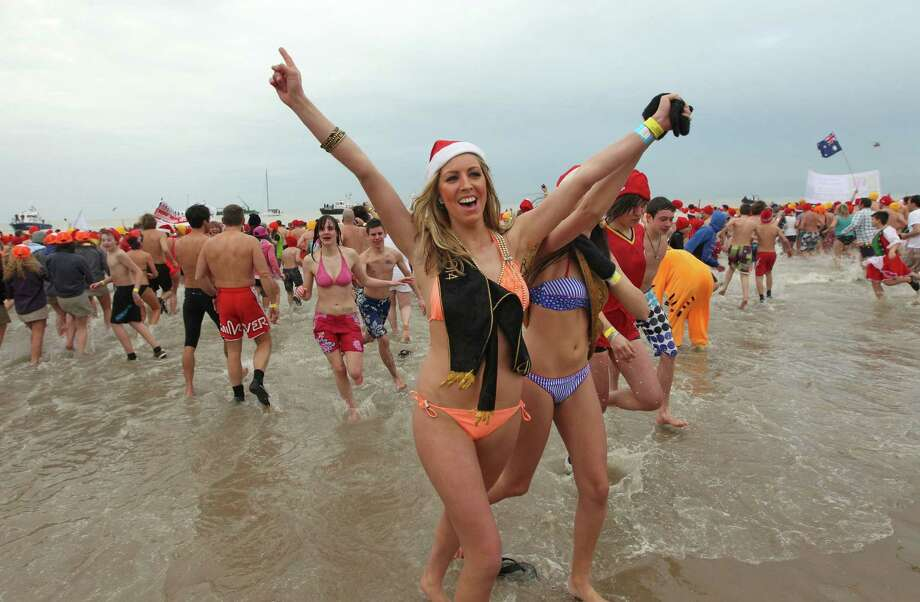 Two women run out of the water, at the Belgian North Sea town of Ostend, Belgium, Saturday, Jan. 4, 2014. Thousands of swimmers jumped and dived into frigid waters as they took part in the annual New Year's plunge into the North Sea. Photo: Yves Logghe, AP  / AP2014