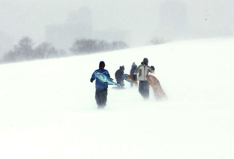 People carry sleds at Montrose Beach Park in Chicago on Sunday, Jan. 5, 2014. Sunday night temperatures will drastically drop to about minus 20 degrees. Photo: Nam Y. Huh, AP / AP