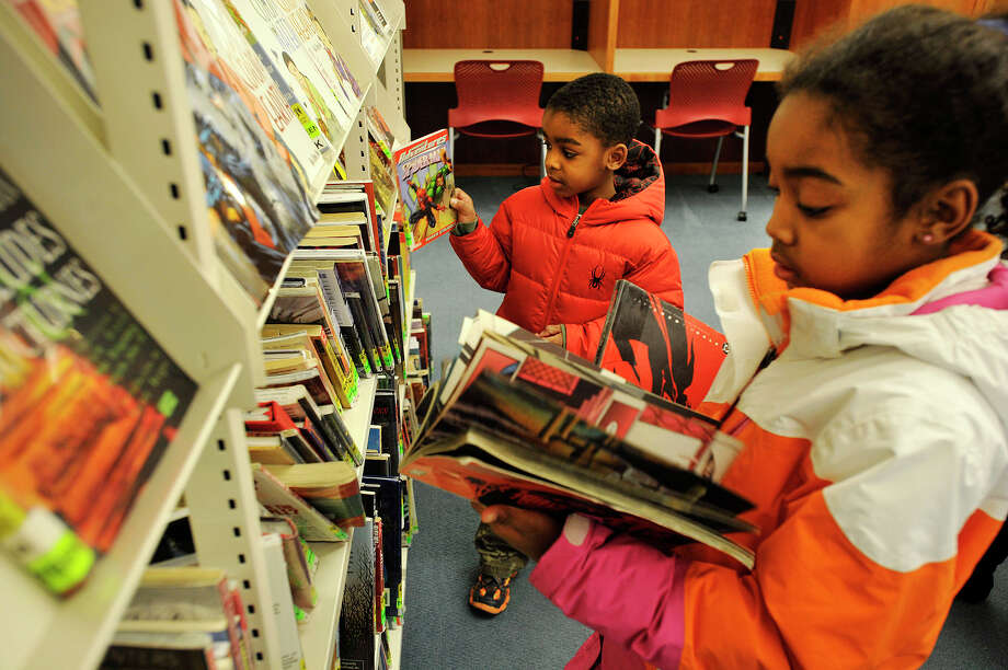 "Evan Myers and his sister, Olivia Myers, look at comic books at the Ferguson Library in Stamford, Conn., on Sunday, Jan. 5, 2014. According to their mother, after watching the movie ""The Avengers"" the two became interested in comic books. Photo: Jason Rearick / Stamford Advocate"