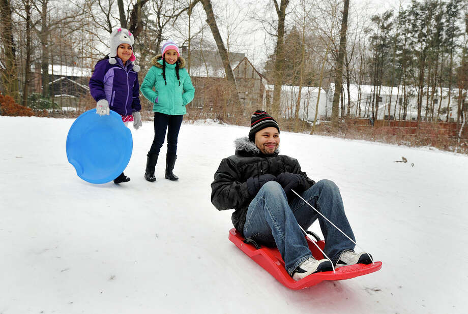 Ishita Sujan, left, and Navya Sharma watch as Navya's father, Gagan Sharma, sleds down a hill at Scalzi Park in Stamford, Conn., on Sunday, Jan. 5, 2014. Photo: Jason Rearick / Stamford Advocate