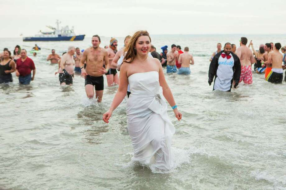 People wade in the water just off the Boardwalk January 1, 2014 at Coney Island in the Brooklyn borough of New York City. Hundreds of people gathered for the annual New Year's Day Polar Bear swim in the ocean. Photo: Christopher Gregory, Getty Images / 2014 Getty Images