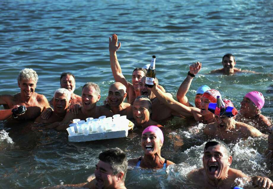 Swimmers toast with champagne in the cold water of the Tyrrhenian Sea during the 'New Year's Dip' (Tuffo di Capodanno) on January 1, 2014 in Livorno, Italy. This year marked the 30th anniversary of the traditional New Year's Day dip, which this year attracted more than 200 swimmers. Photo: Laura Lezza, Getty Images / 2014 Laura Lezza