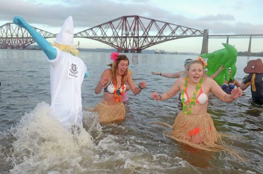 Members of the public wearing fancy dress enter the water as they join around 1,000 New Year swimmers, many in costume, in front of the Forth Rail Bridge during the annual Loony Dook Swim in the River Forth on January 1, 2014 in South Queensferry, Scotland. An estimated eighty thousand people gathered last night in Edinburgh to see in the New Year at Hogmanay celebrations. Photo: Jeff J Mitchell, Getty Images / 2014 Getty Images