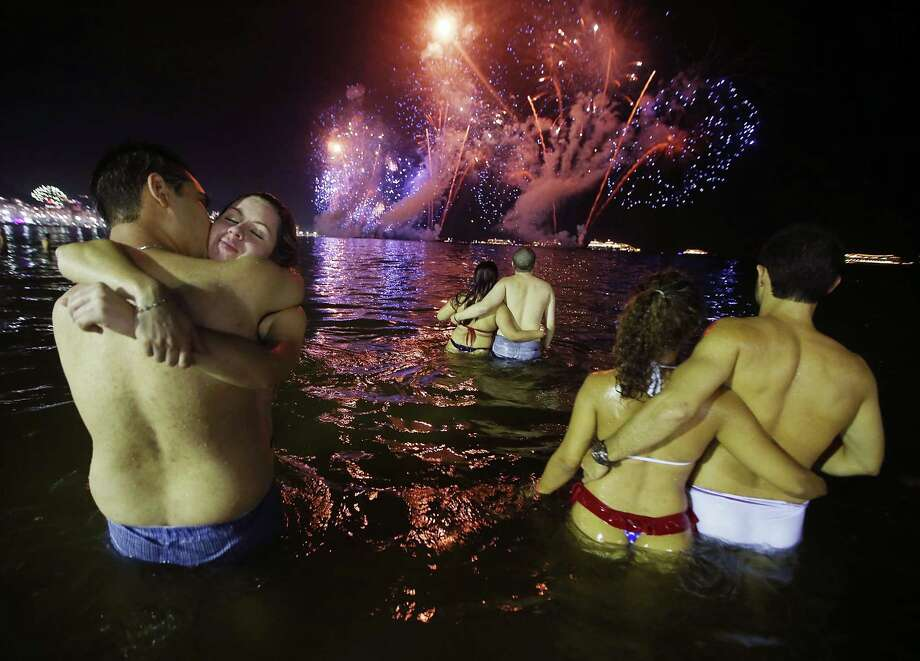 Couple embrace while watching fireworks explode minutes after midnight along Copacabana Beach during New Year's celebrations on January 1, 2014 in Rio de Janeiro, Brazil. More than two million were expected to attend the celebrations at Copacabana to ring in 2014. Brazil is gearing up to host the 2014 FIFA World Cup and the Rio 2016 Olympic Games. Photo: Mario Tama, Getty Images / 2013 Getty Images