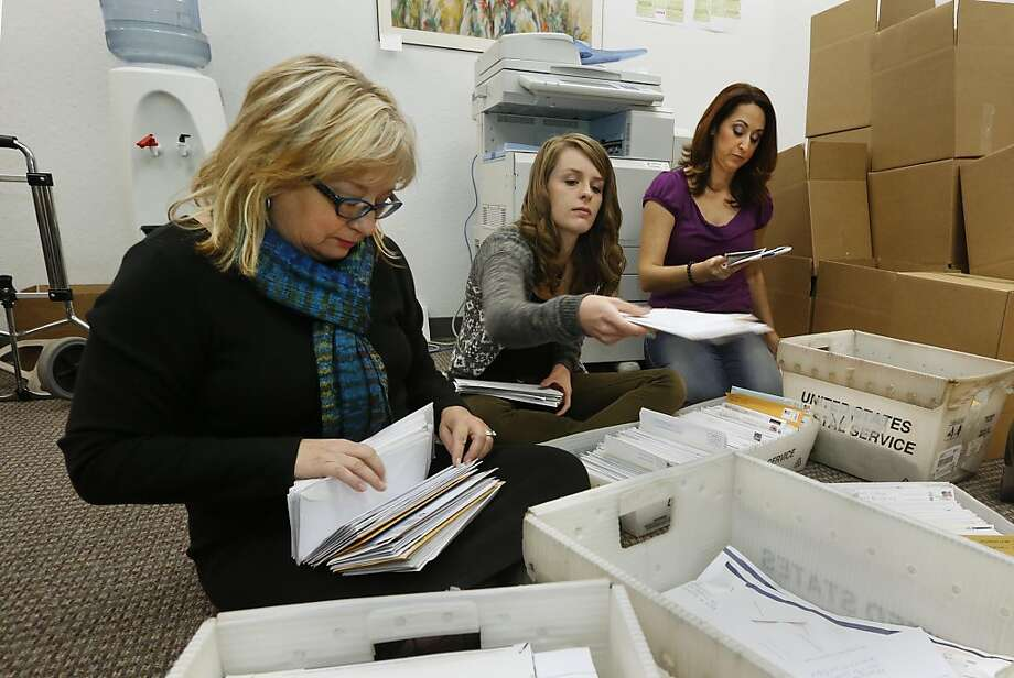 FILE - In this Thursday, Nov. 7, 2013 file photo, Karen England, executive director of the California Resource Institute, left, and volunteers Grace LeFever, center, and Christina Hill, sort through stacks of mail with petitions for a referendum to overturn a new California law that allows transgender students to chose which public school restrooms they use, in Sacramento, Calif. Opponents of the law are working to collect the 504,760 signatures needed to place the referendum on the November 2014 ballot. If approved by voters, the referendum would overturn the law, approved by state lawmakers, that allows transgender students the choice of which restrooms they could use, but also whether to play boys or girls sports. (AP Photo/Rich Pedroncelli, File) Photo: Rich Pedroncelli, Associated Press