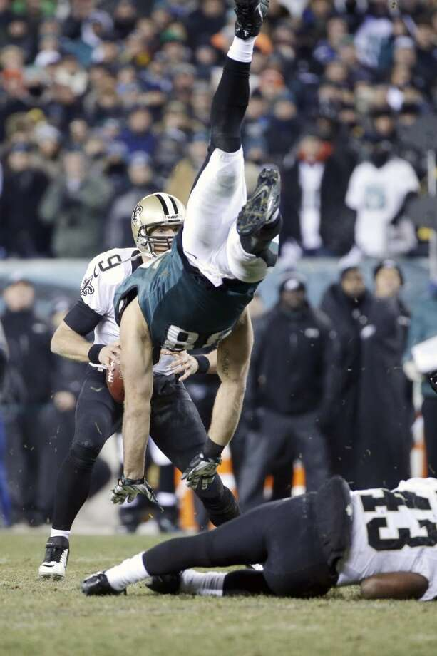 Drew Brees, left, tries to pass as Connor Barwin, center, is upended by Darren Sproles. Photo: Matt Rourke, Associated Press