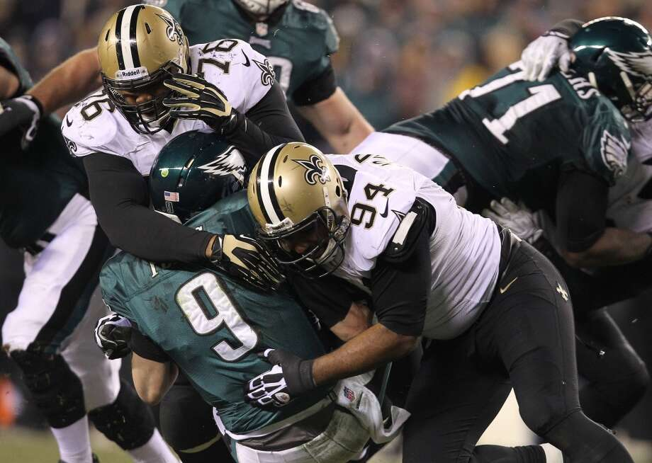 Eagles quarterback Nick Foles (9) is sacked by Akiem Hicks, left, and Cameron Jordan. Photo: DAVID MAIALETTI, McClatchy-Tribune News Service